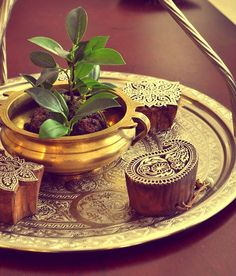 Simple arrangement of block stamps and plant in a brass pot all on a brass plate.