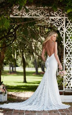 This designer sheath wedding gown from Martina Liana features graphic lace over ivory Imperial crepe. Its sweetheart neckline is accented with sexy spaghetti straps. The back zips up under pearl buttons and flows perfectly into a sleek chapel train.