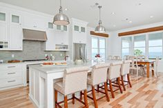 White kitchen with vinyl flooring and gray tile backsplash. Kitchen with chrome bowl pendant lights over kitchen island with marble countertops