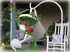 Watering can on shepherd's hook filled with geraniums.