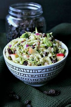Vegan Apple Broccoli Salad is vividly colored in a zigzag patterned black and white bowl. Finely chopped vegetables and fruit fill the bowl.