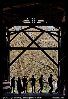 Silhouettes of people dancing inside covered bridge, Felton. California, USA