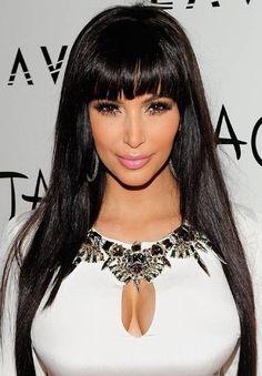 Kim Kardashian piękne, stylowe uczesanie wieczorowe z grzywką, czarne włosy rozpuszczone, kręcone, grzywka pocieniowana.