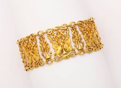 Belle Epoque Musical Instruments Ribbon Bows Gold Bracelet. From the turn of the century comes a delicate and beautifully made Continental 18K gold bracelet of scrolling edged links alternating between narrow segments as ribbon tied trumpets, and wider openwork links featuring violins and cellos, their bows, and crossed trumpets tied in ribbons. 7 3/4 inch x 1 inch. Stamped with the owl mark for French importation.
