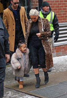 It's a winter wonderland! North West catches a snowflake on her tongue as she heads out in New York with Kim Kardashian on Monday