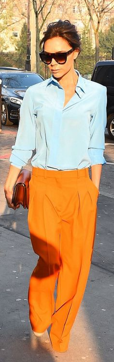 Who made  Victoria Beckham's orange pants, blue collar top, brown handbag, and flat sunglasses?