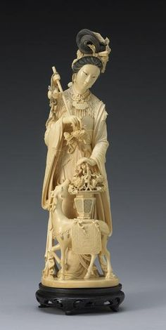 A tinted ivory figure of Magu The Daoist goddess richly jeweled and dressed in layered garments partially covered by an artemisia leaf cape as she stands holding a basket supported on the back of a deer, some of the surfaces highlighted with black wash (age crack). Height 18in (46cm)