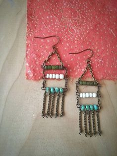 These boho ladder earrings are such a fun pair of earrings! Three beaded bars make up a ladder design and hanging from the bars are antiqued chain fringe. The top two rows are made with Two different types of wood beads and the bottom row consists of lovely turquoise glass beads.  ****  These earrings make a great gift for those who love more earthy tones.  ****  Earrings hang down at approximately 3 from the top of the earwire to the bottom of the fringe and approximately 1 wide. All…