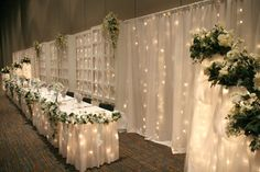 A Wedding at Black Bear Casino Resort with a backdrop of white flowing fabric and white lights behind the head table with the bride and groom and all there attendents.