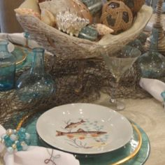 Summer tabletop at Annelle Primos using antique French fish plates and Kim Seybert chargers and napkins.