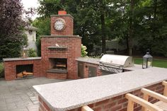 Natural Brick Outdoor Kitchen with Granite Countertop and Fireplace in Huntington, NY. http://greenislanddesign.com/landscape-design-portfolio-outdoor-kitchens.htm