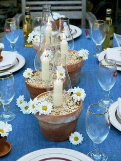 Dark blue denim serves as a table runner for this casual dinner. Terra cotta pots hold chimneys and candles that seem to grow from the pebbles. Tiny pots of daisies sit atop individual plates.