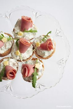 Toasted rye bread rounds with a cream cheese filling topped with a piece of rolled ham. Decorate with a tiny piece of arugula and a mini flower cut from a slice of muenster? Roast Beef Tea Sandwiches, Tea Party Sandwiches, Tapas, Vol Au Vent, Appetizer Recipes, Appetizers, Catering, Reception Food, Party Treats