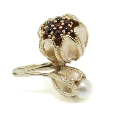 Retro flower ring in 14k yellow gold. This fun vintage piece features two stylized flowers, one holding a pearl and the other opening to reveal a cluster of deep red garnet cabochons, reminiscent of a pomegranate.
