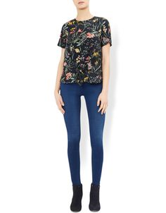 Graphic floral prints bloom across our black Meadow top, designed with a tie-front detail for a wholly modern look. Wear this short-sleeve style with skinny ...