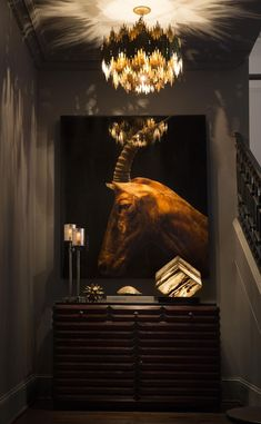 This dark & dreamy alcove by the stairway has an animal vignette. A bold, shiny chandelier hangs above w/ candles on the table providing just the right amount of lighting.