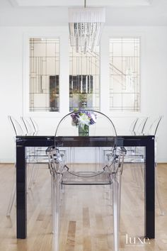 Louis and Victoria Ghost chairs, deep violet Coda table and a Dainolite chrome chandelier