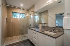 A large mirror covers the wall over the double vanity with neutral countertop, textured rock backsplash and white cabinetry. A sliding glass door leads into the spacious shower with vertical pattern, neutral tile interior. A stone shower floor brings additional texture to finish the design.