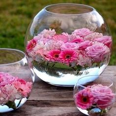 Pink flowers float in a glass fish bowl filled with water #wedding #weddingcenterpiece #cheapwedding