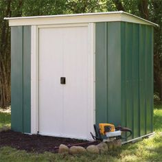 Pent metal shed painted in green and white