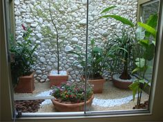 Parede de pedras brancas deixa o jardim de inverno com uma aparência sofisticada.