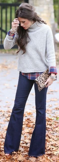 Pale gray sweater over plaid shirt with dark blue jeans.