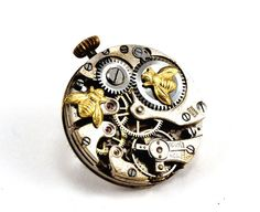 Steampunk brooch which Ive called The Clockedin Worker Bees.  Two tiny industrious little bees are hard at work trying to revive a beautiful antique timepiece. The movement dates from circa 1920s and is wonderfully intricate in a brushed steel with all its original gems. The worker bees stand out against the steel in golden splendour. They have fantastic detail and are absolutely tiny! The winder on the movement at the top adds to the charm of the piece.    Your brooch will be similar to the…