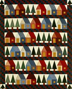 """Provencal Houses:  Visit this dream destination for quilters—a town filled with patchwork houses and pine trees. This delightful village is made in homespun reds, blues, and greens for a warm, country feeling. Designer: Cindy Blackberg. Finished quilt: 84×104"""". Finished house block: 12"""" square. Finished large tree block: 6×12"""". Finished small tree block: 6"""" square."""