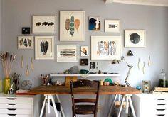 decoração de home office, parede cinza, quadros com molduras brancas, mesa de cavaletes