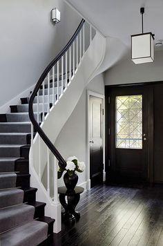 Dunkel gebeitzte Dielen und die geschwungenen Teppe aus schwarz weiß lackiertem Holz geben dem Eingangsbereich des Wohnhauses Eleganz, Ralf Schmitz Immobilien