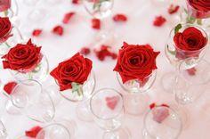 """""""Ein Meer voller Rosen - Statt einen großen Strauß zu binden oder die Blüten regnen zu lassen, kann man rote Rosen auch einzeln in kleine Gläser stellen – schließlich spricht ja jede für sich schon Bände. Am besten über den ganzen Candlelight-Tisch verteilen!"""""""