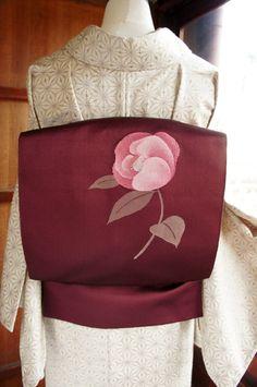 紅紫色を秘めた美しいブラウンの地に、ふっくらとほころんだ咲きかけの蕾を思わせる、ころんと丸い椿の花が一輪織り出された開き名古屋帯です。