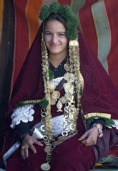 A nomad Tunisian woman girl in a traditional dress poses in front of a tent