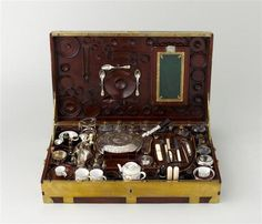 Marie Antoinette's Traveling Case included: a dressing set, desk accessories, sewing kit, glasses and bottles in cut crystal, silver cutlery, porcelain tableware, two coffee cups, tea pot, sweet box, pill box, pair of glasses, a thimble, and a box of medicinal salve.