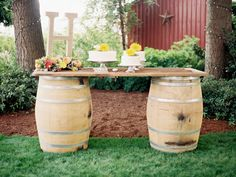 Cake table created from an old door and wine barrels. Outdoor wedding reception on a farm. Photographer: Tara Francis Photography