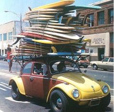 """An interesting photo-trend... overloaded vehicles with surfboards on their roofs. Another VW Beetle """"Bug."""""""
