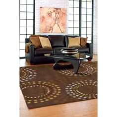 Highlight a treasured piece of furniture with this geometric wool area rug. A rich chocolate brown background showcases the circular shapes in brighter shades that will give your room a contemporary look, and the rug acts as a great accent piece.