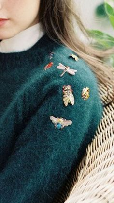 Colorful bug and bee embroidery on a cozy dark green sweater