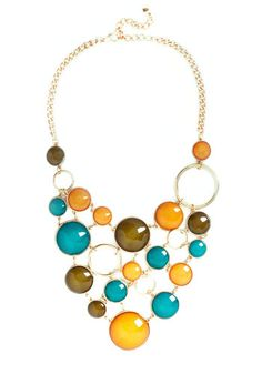 Astronomy Amor Necklace, #ModCloth-- When you're not exploring new galaxies, you're attending elegant galas with this necklace draped over your collarbones. Golden rings and smooth, glitter-filled, teal, sage, and sunshine hemispheres form an abstract bib necklace that's simply stellar. Wear it with a midnight-blue sheath and modern, architectural pumps, and you'll have style down to a science.