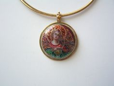 "Karin Pohl- Angel inspired by Fra Angelico 15c. Enamels w/ Foils, 24k YG Paillons & Granules; Fabricated Setting S/S, 14k, 22k YG; 4mm Faceted Yellow Sapphire; Size: 1 7/8"" x 1 1/4"""