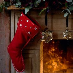Fireplace decorated with red felt stocking, eucalyptus, rose blooms and pine cones