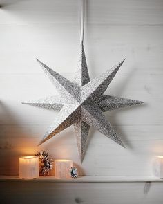 Astronomical Accent - Evoke the grandeur of VY Canis Majoris -- the largest star in the known universe -- with this two-foot-wide shimmery wonder. It's easier to make than you might think: Construct two four-pointed stars from folded squares of card stock covered with silver glitter, then glue together. #marthastewart #crafts #diy