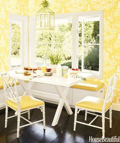 Printed yellow wallpaper, white dining table, and yellow and white chairs