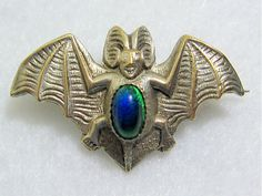Art Nouveau silvertone bat brooch wth irridescent glass belly.
