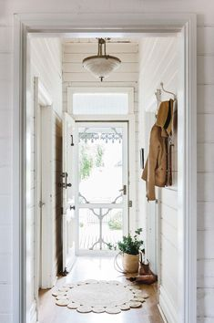 The small entryway of this country farmhouse is so charming. The white shiplap and white walls make a small space appear bigger by adding extra light. Definitely interior decorating inspiration goals. #interiordecorating #farmhousestyle #decoratinginspiration #countryfarmhouse
