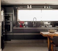 A cozinha tem bancada de mármore negro e armários da mesma cor. No corredor, quadros com pintura estilo bico de pena, de Itiberê Massulo. Apartamento do arquiteto paulista Ricardo Caminada (Foto: Victor Affaro/Casa e Jardim)