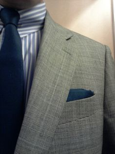 Light grey POW check suit with blue and white stripe pin collar shirt and navy tie.