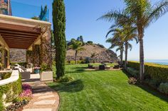 Yolanda Foster backyard extended roof tall trees stone pathway chairs manicured hedges