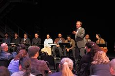 Director Jonathan Salisbury talks to the audience, backed by the Cast of the reading