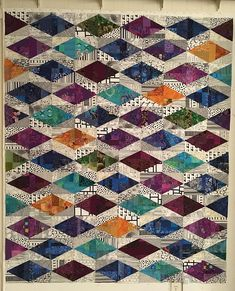 In the winter of 2016 Lynne Tyler made three quilts using scraps and the Tri-Recs template set. This tutorial explains the process from start to finish, and shows photos of the finished quilts, Fruit Loops, Treasure Trove and Snow Day. Use your scraps to build large slabs or made fabric, then cut the blocks from this made fabric. The tutorial shows step by step instructions to make the slabs, cut the blocks and the side triangles, and assemble the blocks. The basic block can be arranged…
